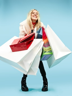 Full length portrait of a beautiful smiling funny blonde woman walking with colorful shopping bags isolated over blue studio background.