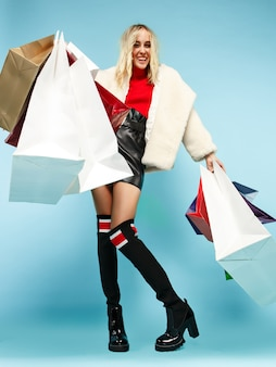 Full length portrait of a beautiful smiling funny blonde woman walking with colorful shopping bags