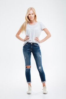 Full length portrait of a beautiful smiling girl with her arms on hips isolated on the white wall