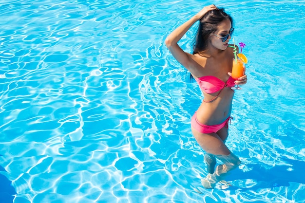 Full length portrait of a beautiful woman drinking cocktail in swimming pool