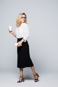 Full length portrait of beautiful young business woman in formal wear walking and texting on cell phone with takeaway coffee in hand isolated over gray wall.
