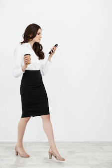 Full length portrait of beautiful young business woman in formal wear walking and texting on cell phone with takeaway coffee in hand isolated