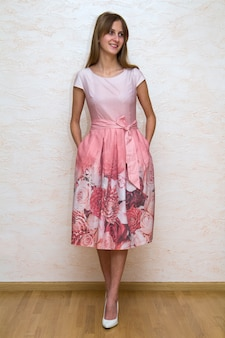 Full length portrait of a beautiful young happy confident girl with long blond hair posing in summer dress with pink floral design and white high heels. youth and beauty concept.