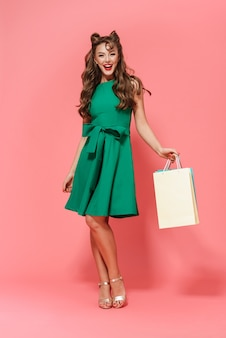 Full length portrait of a beautiful young pin-up girl wearing dress standing isolated, carrying shopping bags