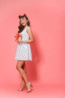 Full length portrait of a beautiful young pin-up girl wearing dress standing isolated, showing gift box