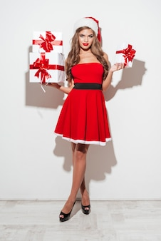 Full length portrait of a beautiful young woman in red christmas costume holding stack of presents isolated