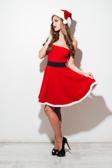 Full length portrait of a beautiful young woman in red santa claus dress posing and looking away isolated over white surface