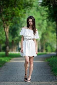 Full length portrait of a beautiful young woman in white dress with open shoulders, clean skin, long hair and casual makeup