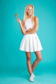 Full length portrait of a beautiful young woman with long hair holding lollipop and looking at camera isolated on the blue background