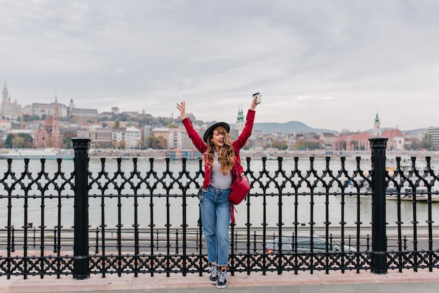 Full-length portrait of blissful lady in red jacket posing with hands up on embankment