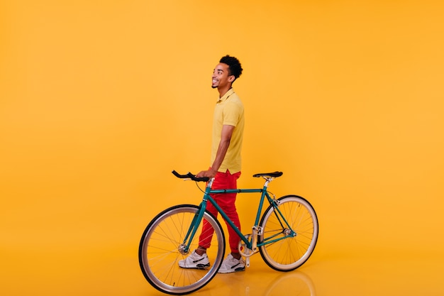 Full-length portrait of blithesome african man posing with bicycle. photo of trendy black guy in sport shoes standing.