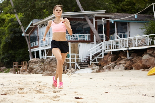 Full length portrait of blonde female runner in sportswear and pink sneakers jogging on beautiful sandy beach having determined serious expression while training for marathon.
