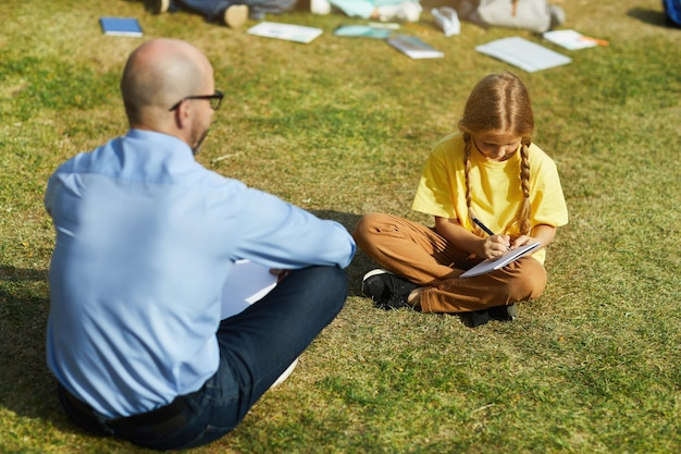 Full length portrait of blonde teenage girl sitting on green grass in sunlight and writing in notebook during outdoor class with teacher, copy space