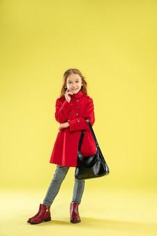 Un ritratto integrale di una ragazza caucasica alla moda luminosa in un impermeabile rosso che tiene una borsa nera su colore giallo