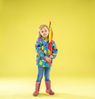 Un ritratto a figura intera di una ragazza alla moda brillante in un impermeabile che tiene un ombrello dei colori dell'arcobaleno sul giallo.