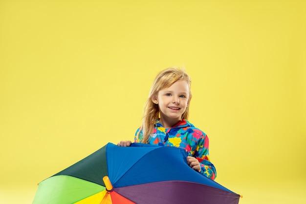 Un ritratto a figura intera di una ragazza alla moda brillante in un impermeabile