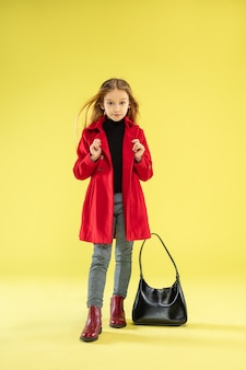 A full length portrait of a bright fashionable girl in a red raincoat with black bag posing on yellow studio wall