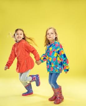 Un ritratto a figura intera di ragazze alla moda luminose in un impermeabile che si tengono per mano, correndo e divertendosi sulla parete gialla dello studio