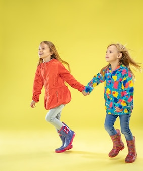A full length portrait of a bright fashionable girls in a raincoat holding hands, running and having fun on yellow studio wall.