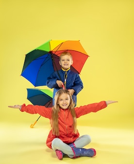 A full length portrait of a bright fashionable kids in a raincoat