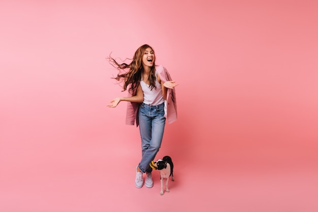 Full-length portrait of brunette lady in jeans posing with dog. indoor portrait of beautiful female model standing beside french bulldog.