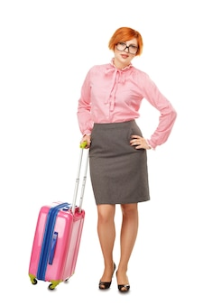 Full length portrait of a business woman in glasses  in business trip standing with a pink travel suitcase