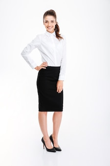 Full length portrait of a businesswoman standing with hand on hip isolated on a white wall