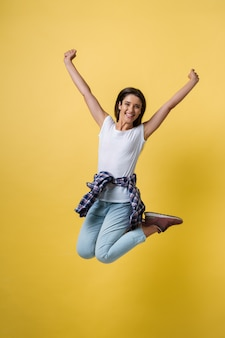 Full-length portrait of carefree girl in white shirt and jean jumping on yellow background.