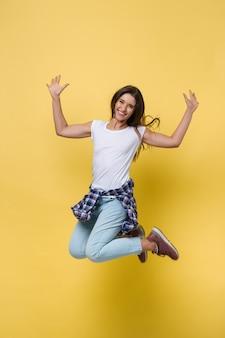 Ritratto a figura intera di ragazza spensierata in camicia bianca e jeans che saltano su sfondo giallo.
