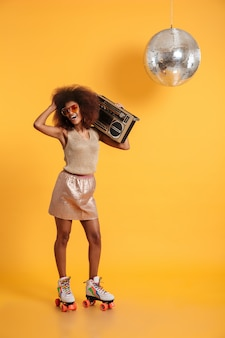 Full length portrait of charming african woman in retro clothes standing on roller skates, holding boombox, touching her afro hairstyle
