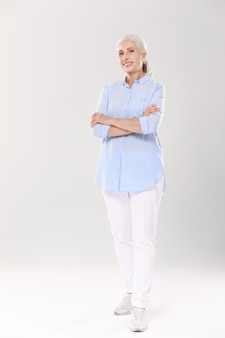 Full-length portrait of charming old lady in blue shirt and white pants, standing with crossed hands