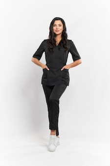 Full length portrait of charming professional beautician in black medical uniform standing on white