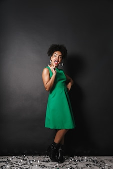 Full length portrait of a cheerful afro american woman wearing dress standing over black wall