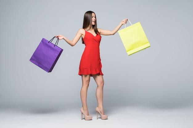 Ritratto integrale di una donna attraente allegra che tiene il sacchetto della spesa isolato su una parete bianca
