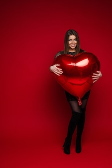 Full length portrait of cheerful brunette girl in dress and boots embracing red heart-shaped balloon on red background. saint valentine concept.
