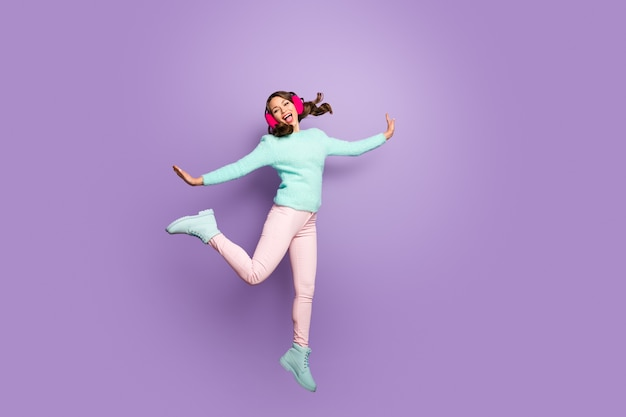 Full length portrait of cheerful energetic girl jump rest relax enjoy moving wear pink ear covers pastel footwear.
