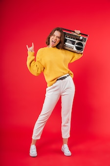 Full length portrait of a cheerful girl with a boombox