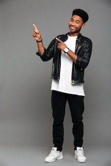 Full length portrait of cheerful handsome african man in stylish wear pointing with two fingers, looking
