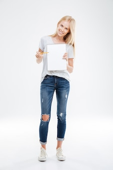 Full length portrait of a cheerful happy pretty girl pointing pencil at blank notebook isolated on the white wall