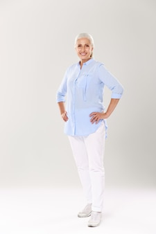 Full-length portrait of cheerful mature woman in blue shirt and white pants, standing with hands on her waist