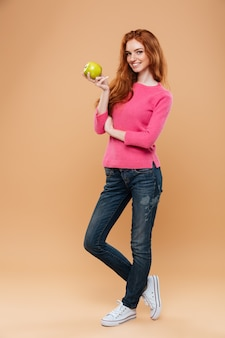 Full length portrait of a cheerful pretty redhead girl holding apple