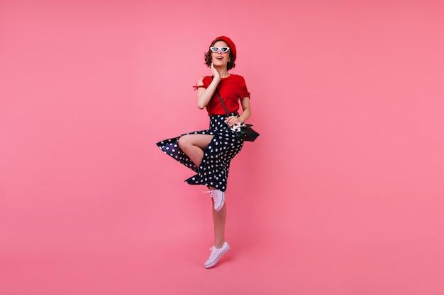 Ritratto integrale della ragazza allegra ben vestita divertendosi. debonair signora francese con i capelli castani corti che balla.