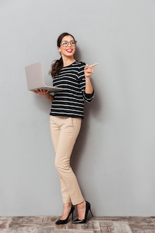 Full length portrait of a cheerful woman in eyeglasses