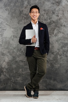 Full length portrait of a cheerful young asian man