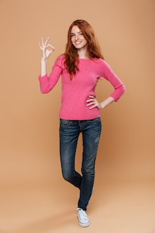 Full length portrait of a cheery smiling redhead girl making the ok gesture