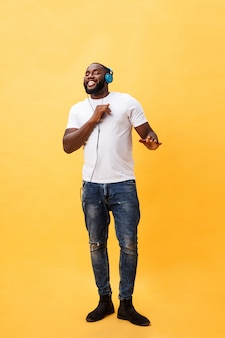 Full length portrait of a cherry young african american man listening to music with headphones