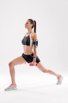 Ritratto integrale di una donna di forma fisica concentrata in abiti sportivi