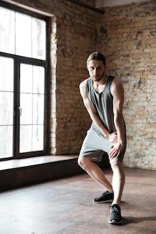 Il ritratto integrale di uno sportivo concentrato che fa l'allungamento si esercita