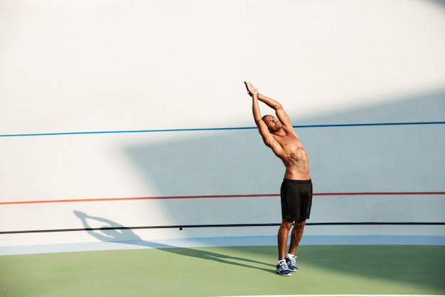 Full length portrait of a concentrated sportsman doing stretching