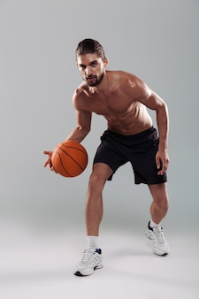 Full length portrait of a concentrated young shirtless man